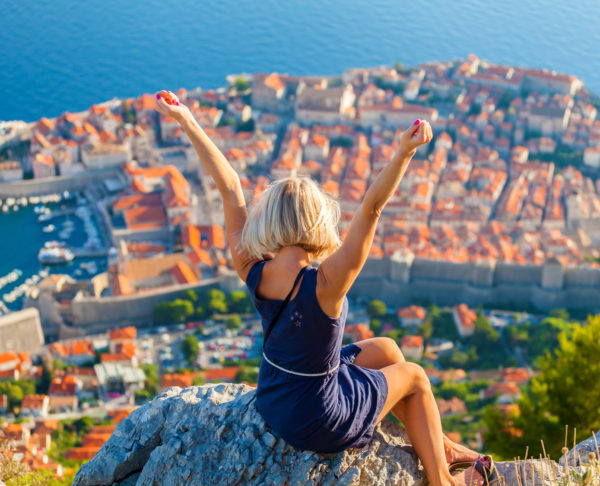 Young woman tourist looks to the old city of Dubrovnik.