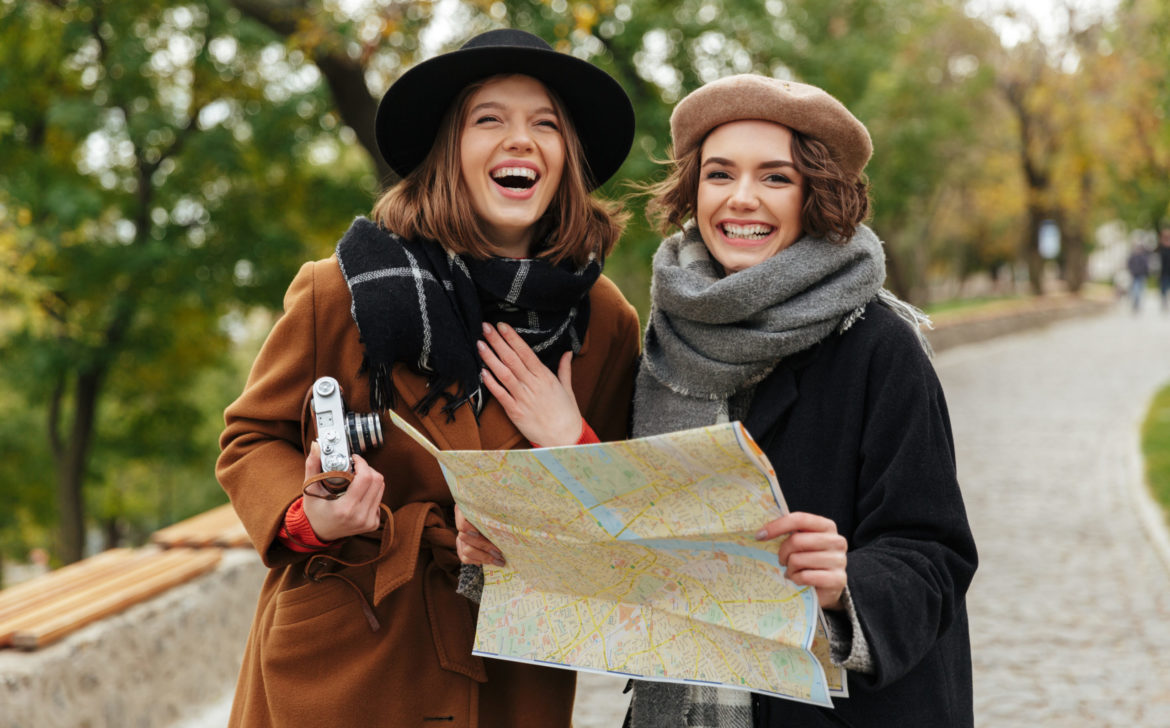 Portrait of two happy girls dressed in autumn clothes