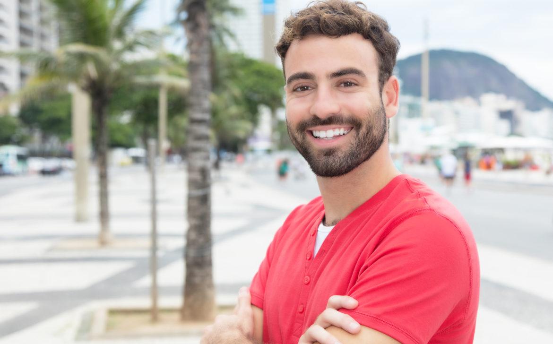 Modischer junger Mann mit Bart und rotem Shirt in der Stadt
