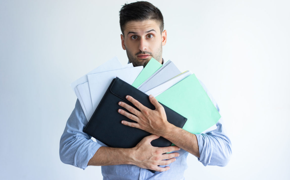 Puzzled office worker holding pile of documents
