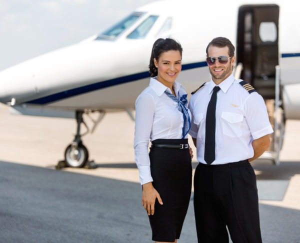 Happy Airhostess And Pilot Standing Against Private Jet